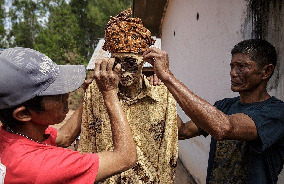 Семья Тиранда надевает солнечные очки своему покойному родственнику во время ритуала Манене, который