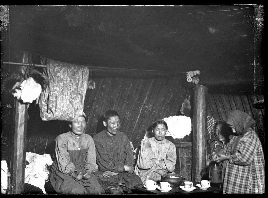 Интерьер якутского чума и группа сидящая вокруг чайных чашек, 1902