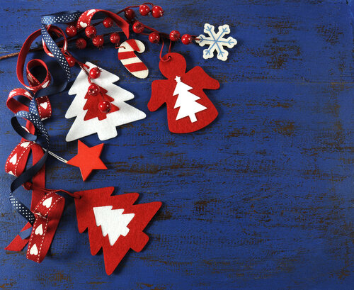 Christmas holiday festive natural style wood and felt ornaments on a dark royal blue vintage recycled wood background.