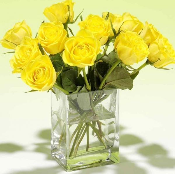 В прозрачной четырехгранной вазе стоит букет  желтых роз