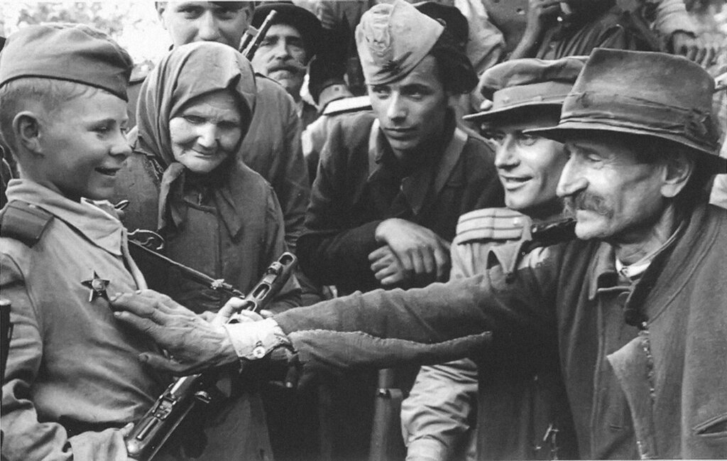 Командир стрелкового батальона В. Романенко (второй справа) рассказывает жителям одного из селений в районе Белграда о боевых делах юного разведчика – Вити Жайворонка. Старчево, Югославия, октябрь 1944