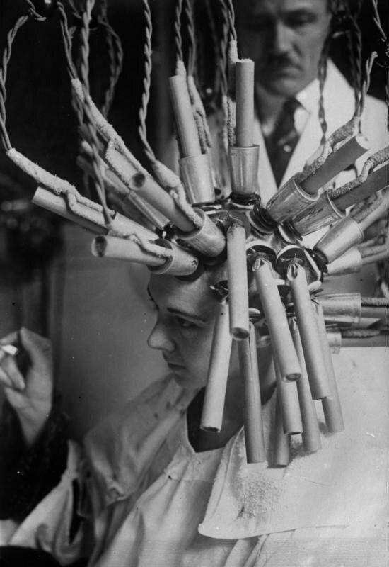 Keine Raketenmaschine, sondern ?... ein Apparat zur Herstellung von Dauerwellen !Eine Dame beim Ondulieren ihres Haares mittels eines Dauerwellen - Apparates.Die aus diese Weise hergestellten Dauerwellen halten ein Jahr.