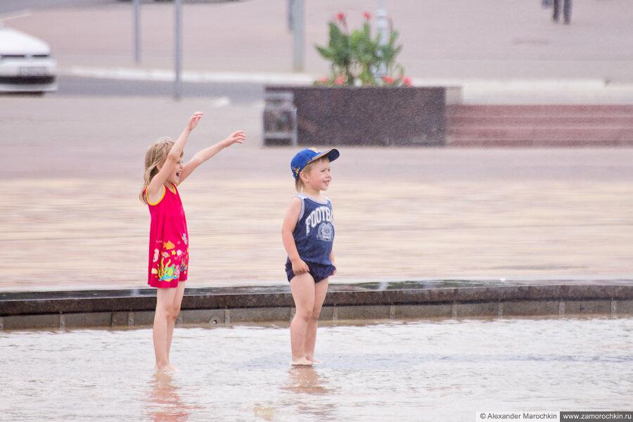 Дети радуются брызгам у фонтана