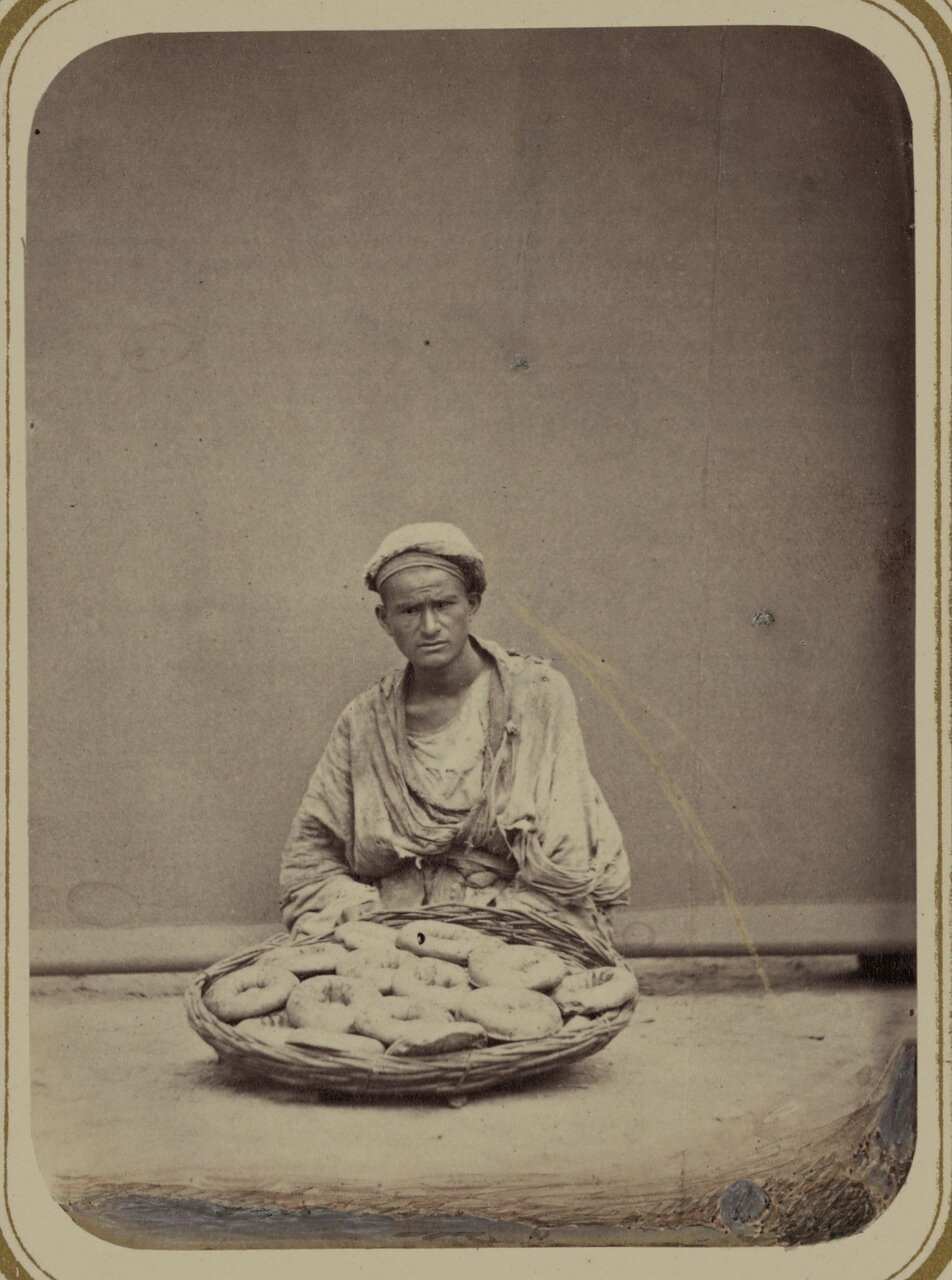 Пекарное производство. Продавец лепешек, осыпанных кунжутными семенами