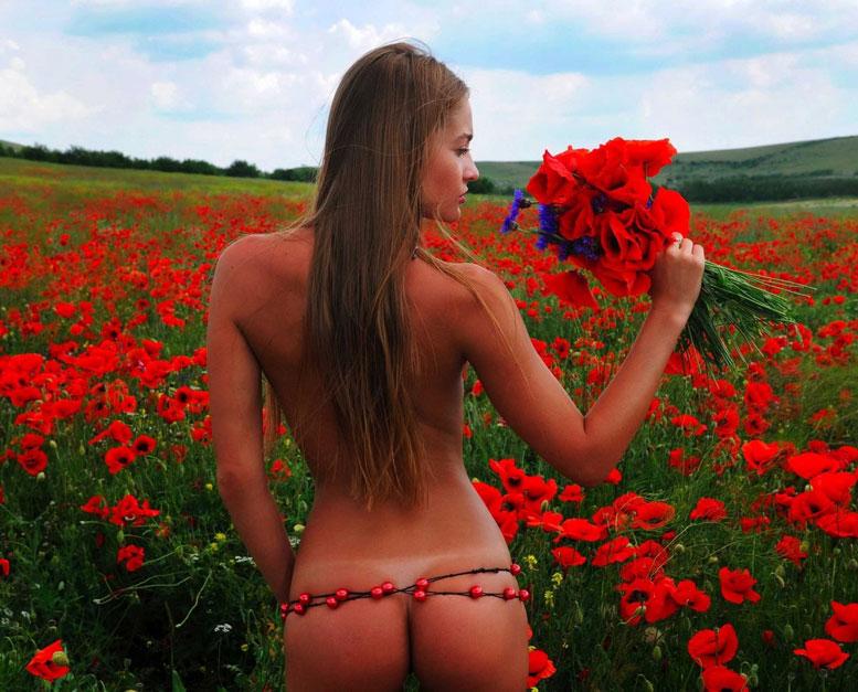 голая девушка в поле с красными цветами