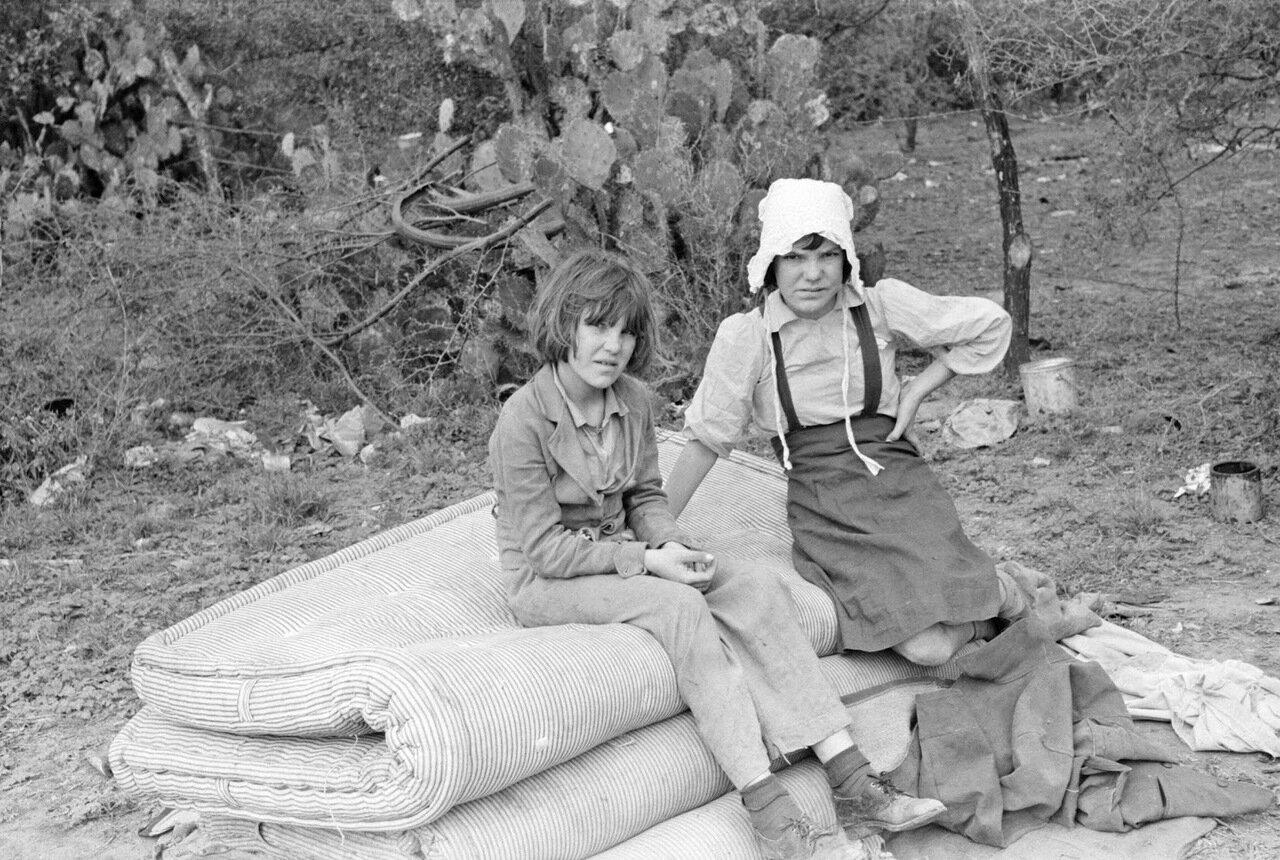 Дети сезонных рабочих из западного Техаса, сидят на матрацах, только что выгруженных из трейлера. Харлинген, Техас, 1939