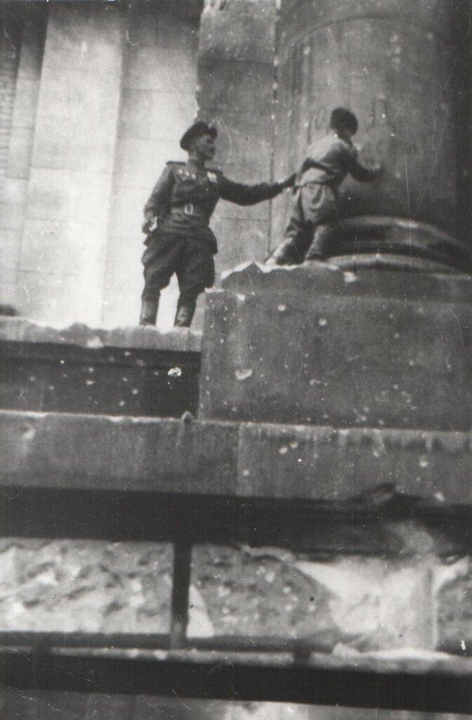 Сын полка Володя Тарновский ставит автограф на колонне Рейхстага. Май 1945