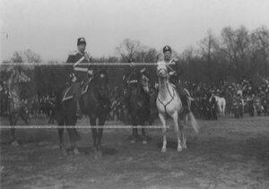Николай II и сопровождающие его офицеры принимают парад лейб-гвардииКазачьего полка на военном поле.