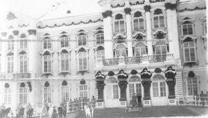 Император Николай II и члены императорской фамилии у подъезда дворца наблюдают за смотром полка.