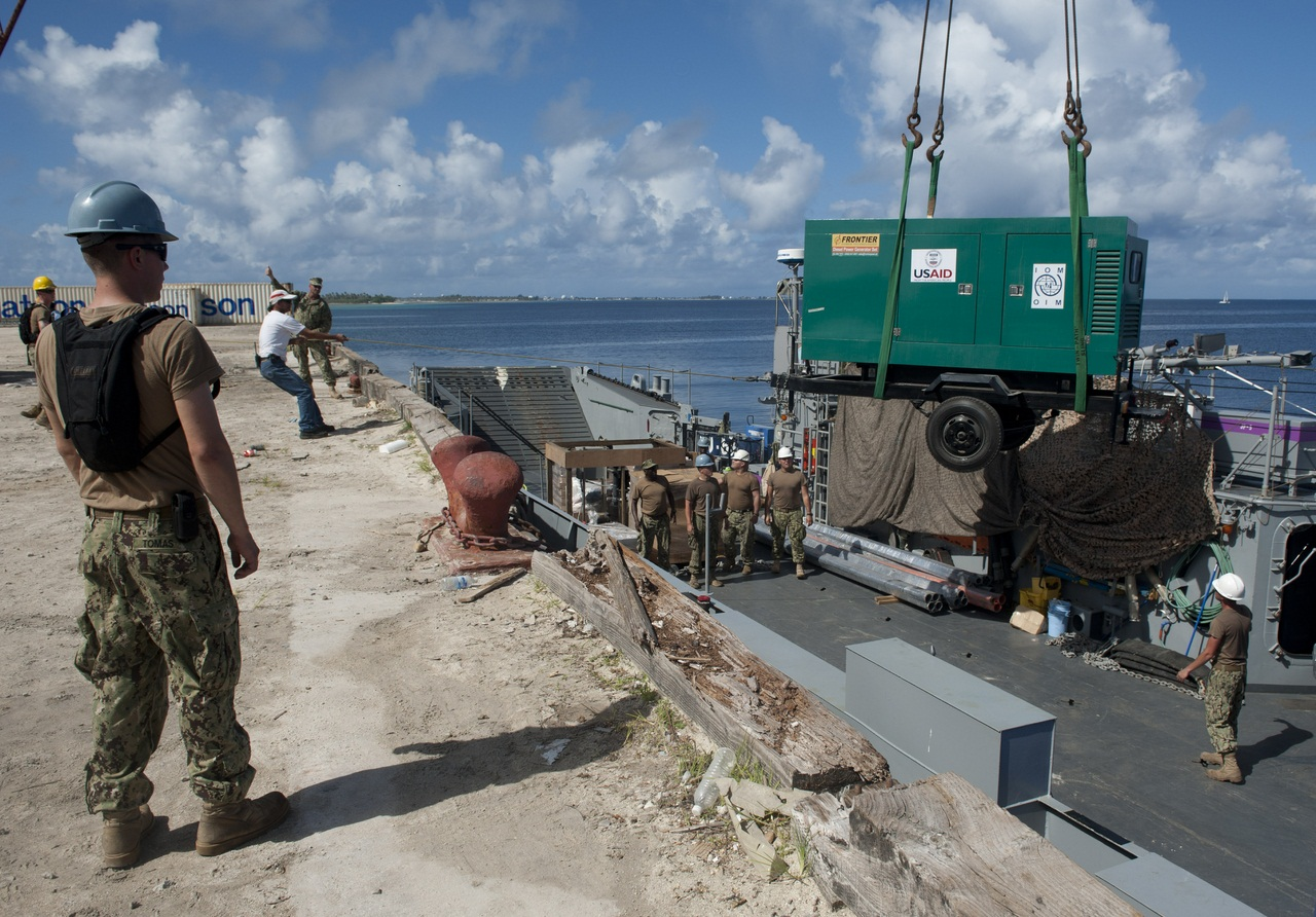 130707-N-SK590-259 EBEYE, Marshall Islands (July 7, 2013) U.S. Navy Sailors and Marshallese pier workers unload a reverse osmosis water system from a landing craft utility (LCU) during Pacific Partnership 2013. The filtration unit, provided by the U.S. A