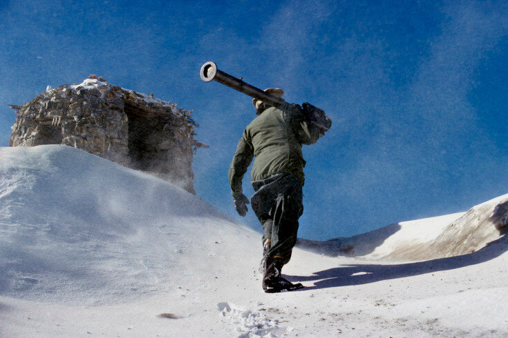 02.1_130: February, 1988 An Afghan mujahideen fighter carries a US-made stinger missile up a hill near Jaji, Afghanistan. February, 1988