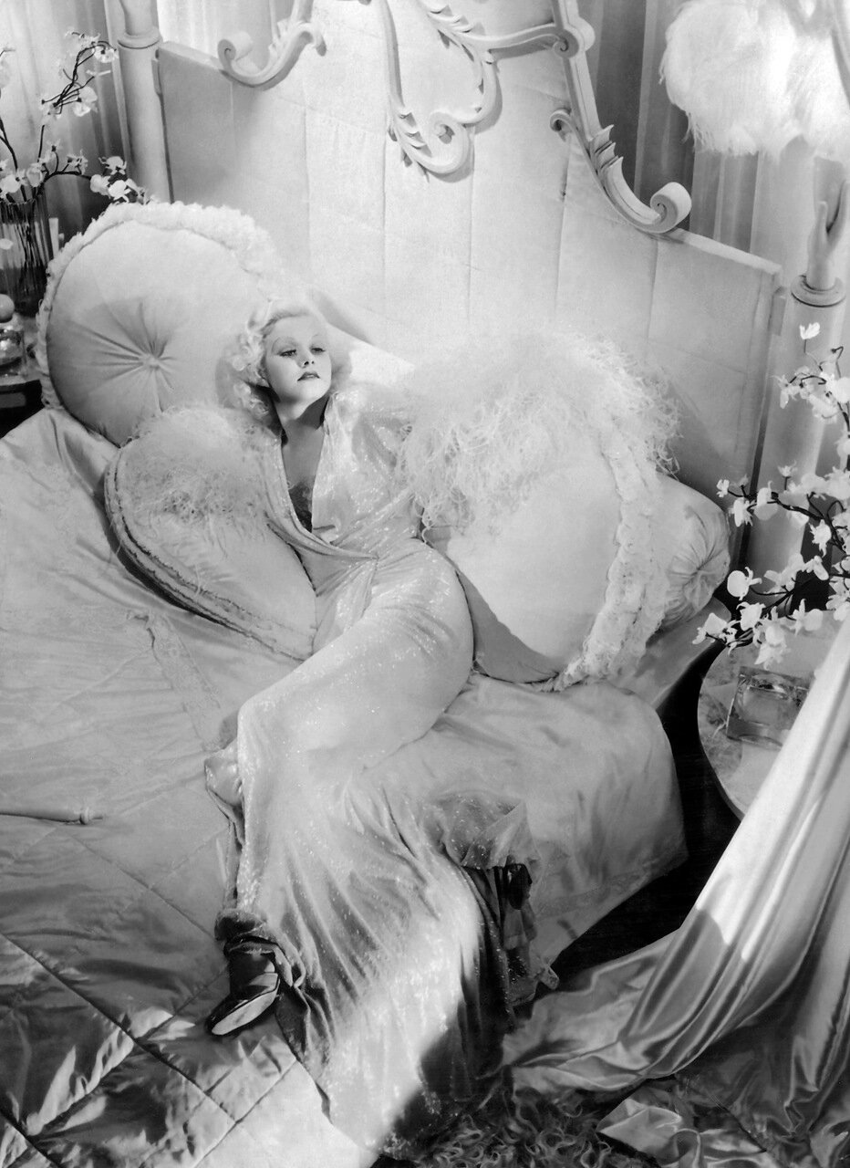 1933: The American 'platinum blonde' leading lady Jean Harlow (1911 - 1937), formerly Harlean Carpentier, reclining in a luxuriant white sequined negligee, probably designed by Adrian. Title: Dinner at Eight (Photo by Margaret Chute)