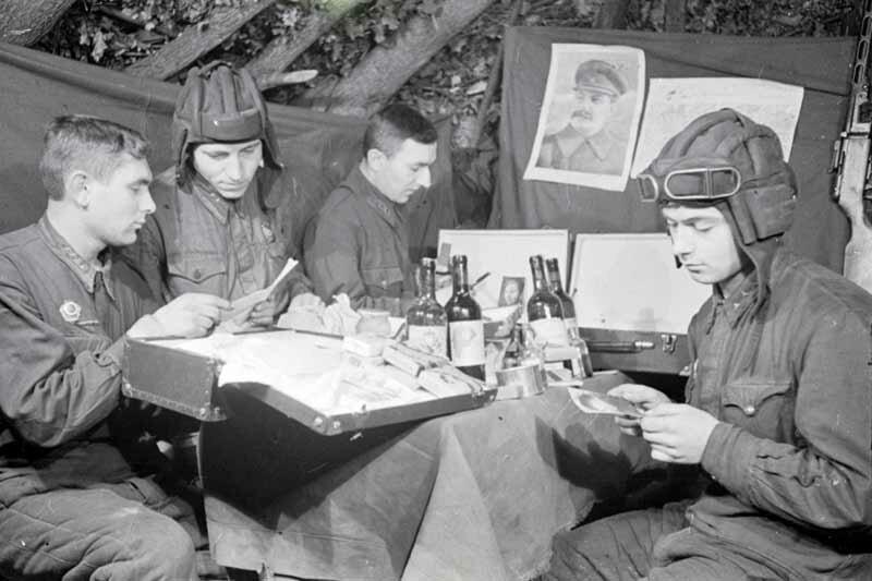 Экипаж танка Н-ской части: старшина Н.В.Жернов, старший сержант И.В.Ладов, лейтенант Д.В.Фильненко и старший сержант Лебедев рассматривают подарки и читают письма, полученные от трудящихся Саратовской области. 1943