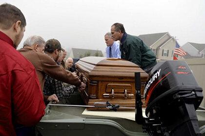 На кладбище был привезён гроб рыболова в небольшой моторной лодке