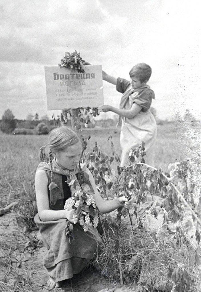 Пионеры Таня Кострова и Маня Михеева ухаживают за братской могилой в освобожденном от немцев селе. 1942 г.