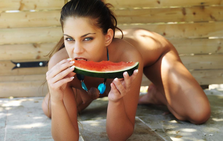 голая девушка с арбузом во рту
