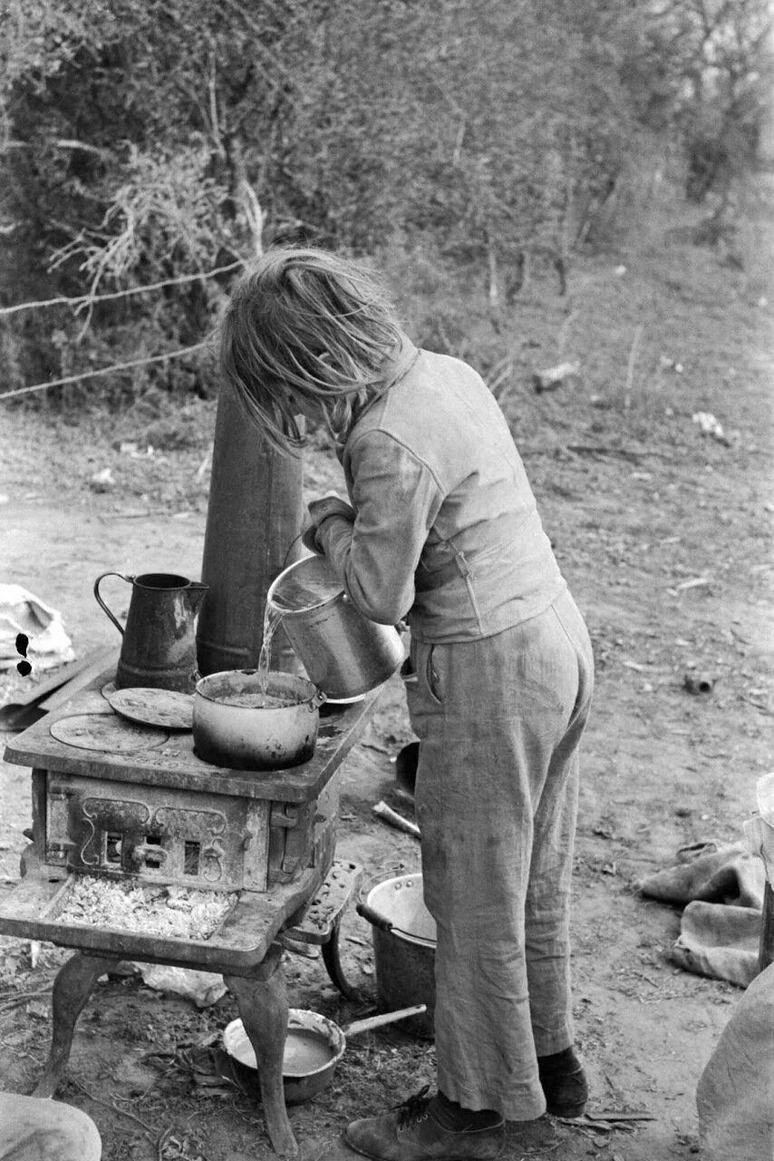 Ребенок сезонных рабочих добавляет воду в кипящие бобы на плите, вблизи Харлингена, Техас, 1939