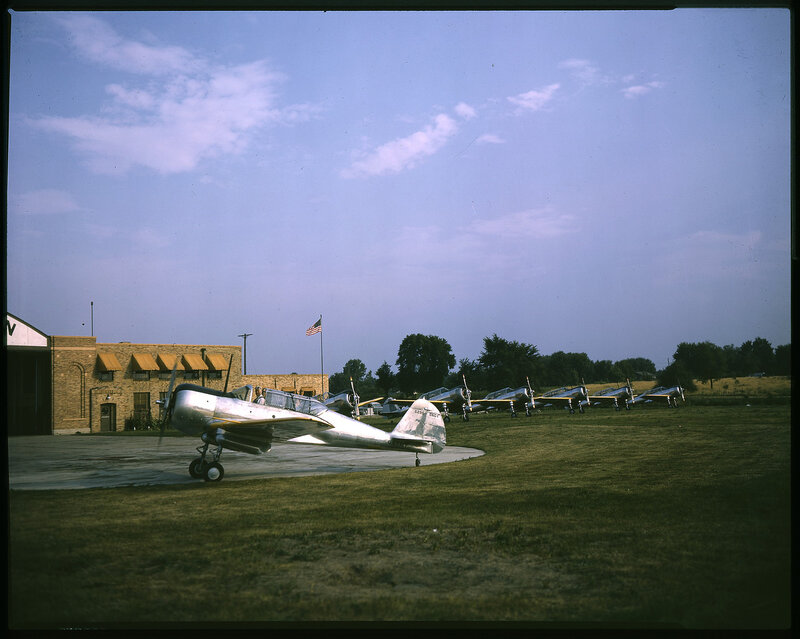 One-quarter left front view of Curtiss SNC-1 Falcon (CW-22N) (BuNo 6298) taxing.  Other SNC-1's are visible in the background.  An unidentified aircraft hangar is visible in the background.