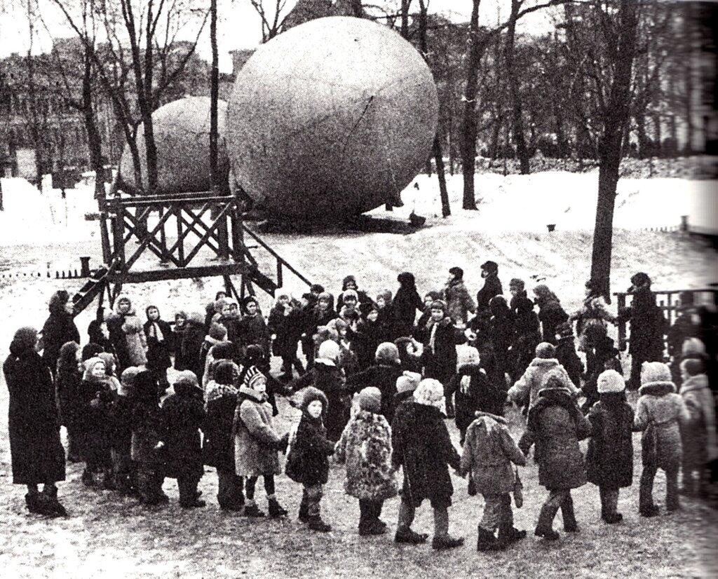 Дети водят хоровод на фоне аэростатов воздушного заграждения. Скорее всего — начало зимы 1941 года.  Москва.