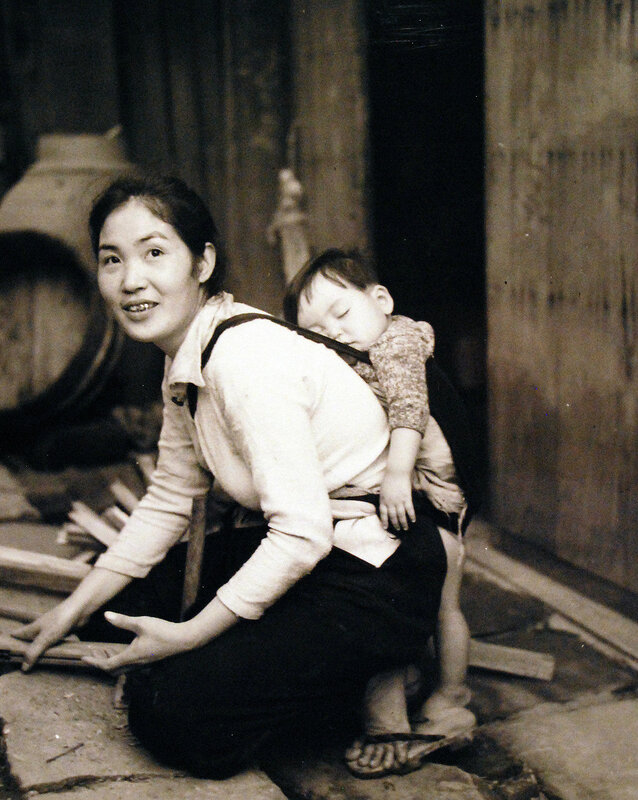 Scene at Sasebo, Kyushu, shows mother working with sleeping child on her back.  October 19, 1945