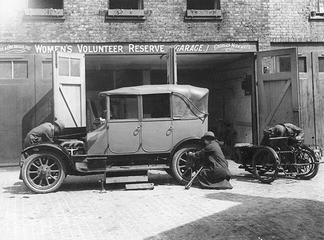 Mechanics repairing a car at a Women's Volunteer Reserve motor garage