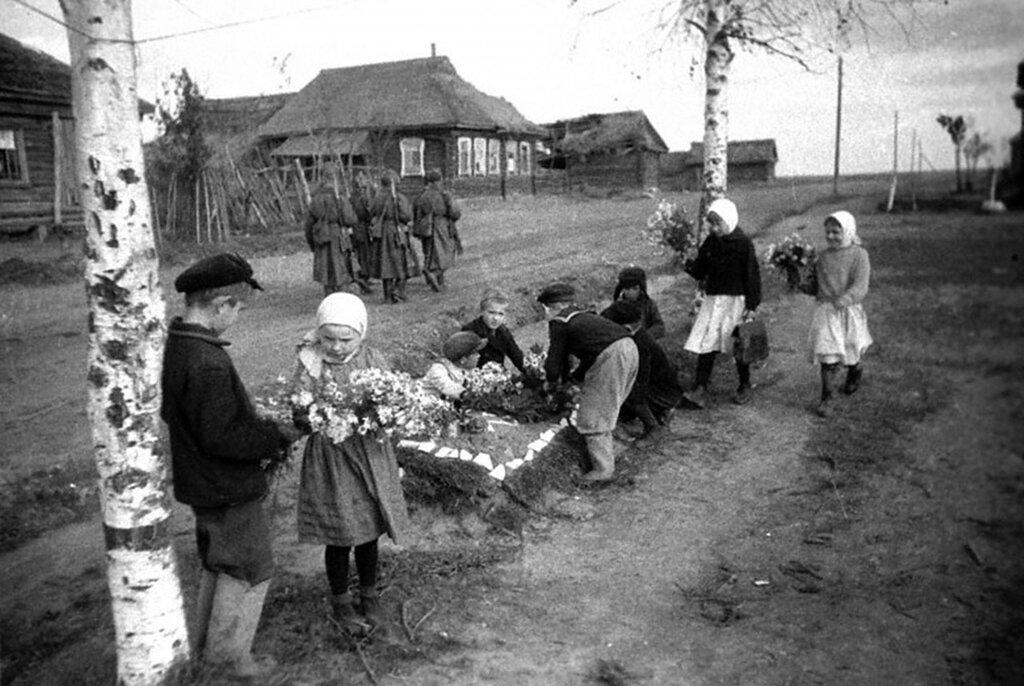 Дети освобожденного г.Ржева Калининской обл. возлагают цветы на могилы советских бойцов. 1942 г.