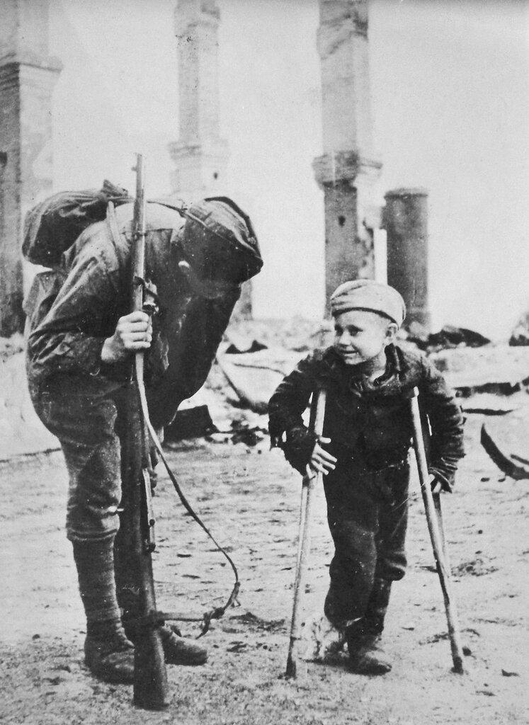 Неизвестный боец Красной Армии беседует с десятилетним Володей Лукиным, родителей которого немцы угнали в Германию. Лишившись крова, мальчик отморозил себе ноги. 2-й Прибалтийский фронт. 1944 год.