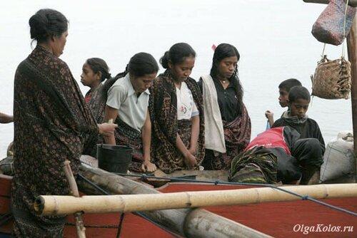 Женщины, завернутые в икат, на пляже Wodong рядом с Маумере
