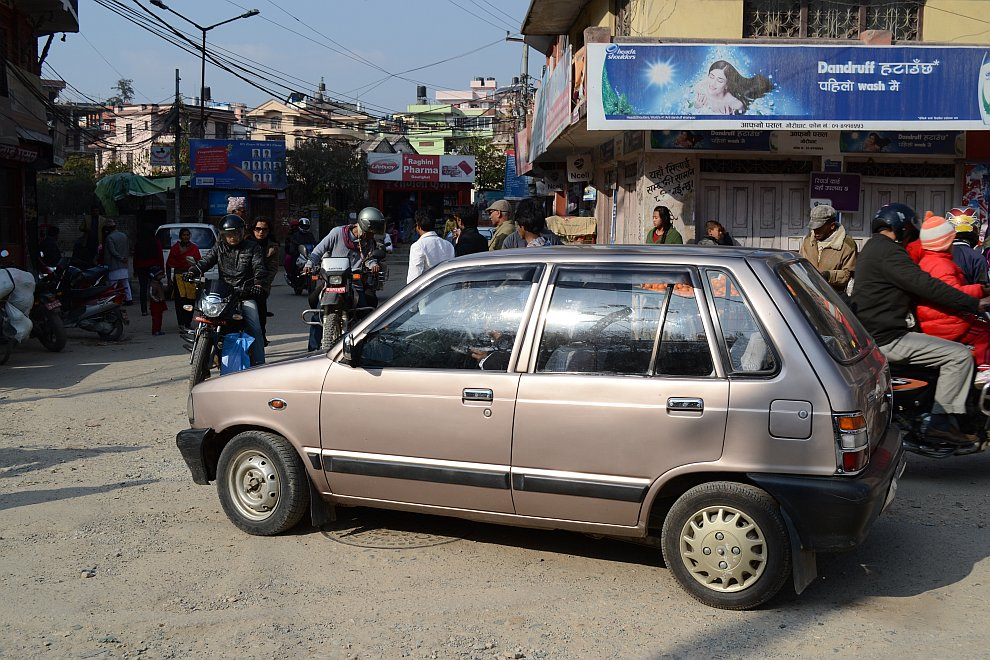 Белая букашка — такси на 8 человек с багажом. Для представления о размерах рядом Тойота Лэнд Круизер