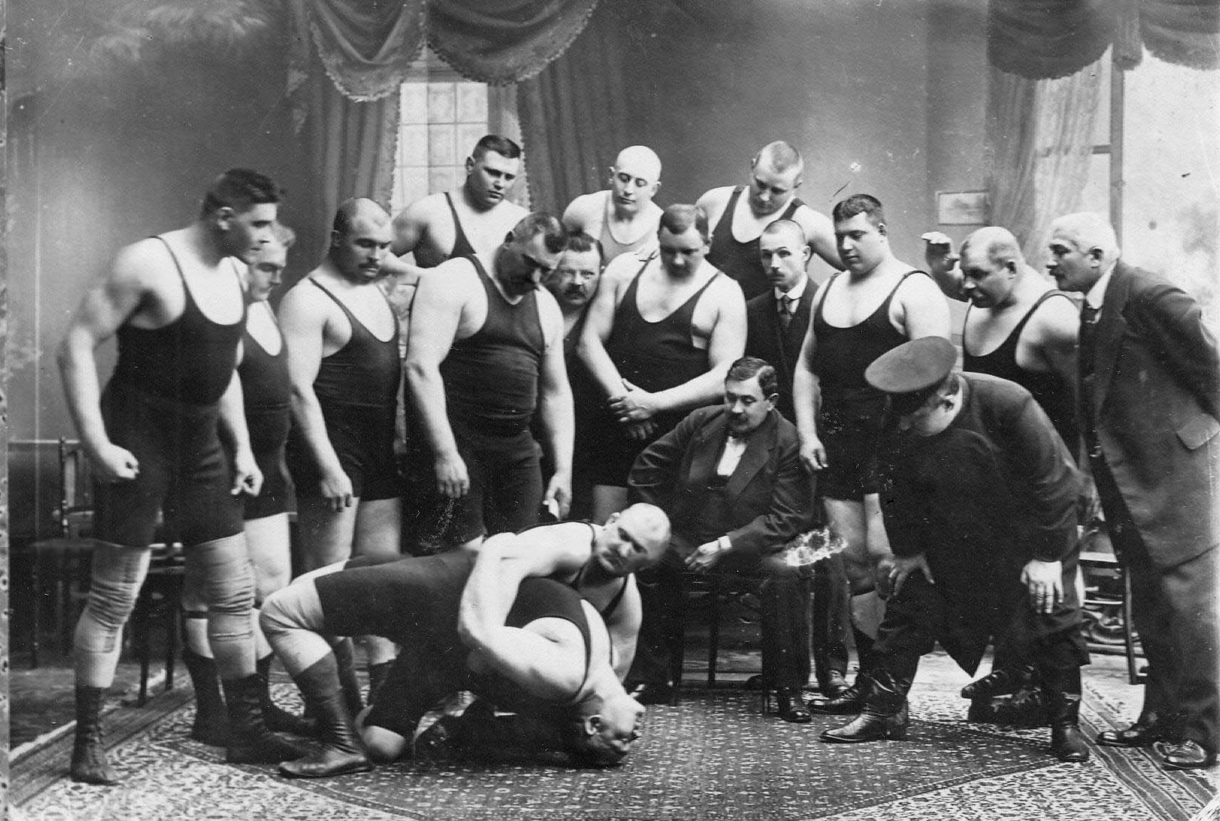Группа участников чемпионата наблюдает за борьбой двух борцов