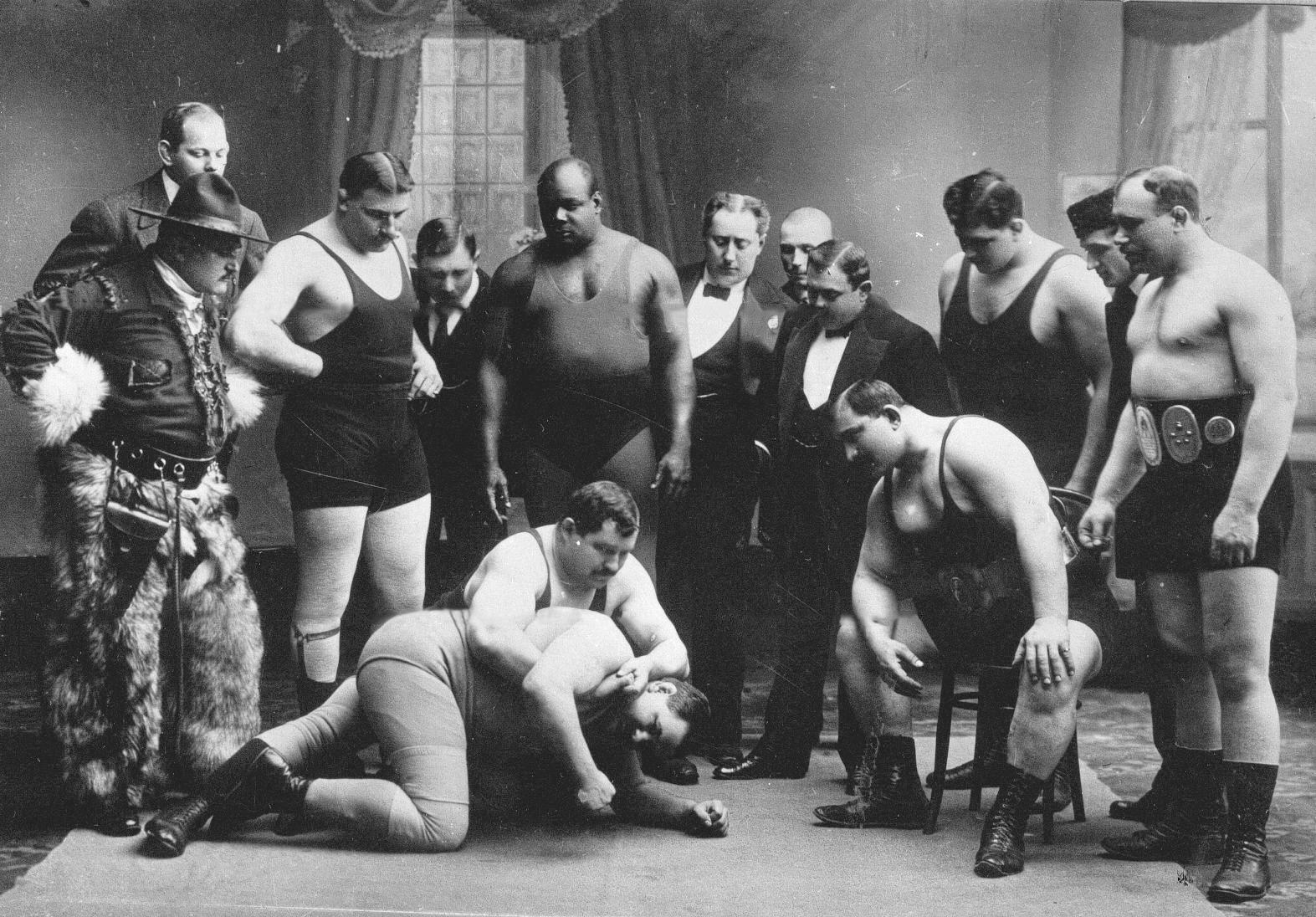 Группа участников чемпионата наблюдает за схваткой двух борцов