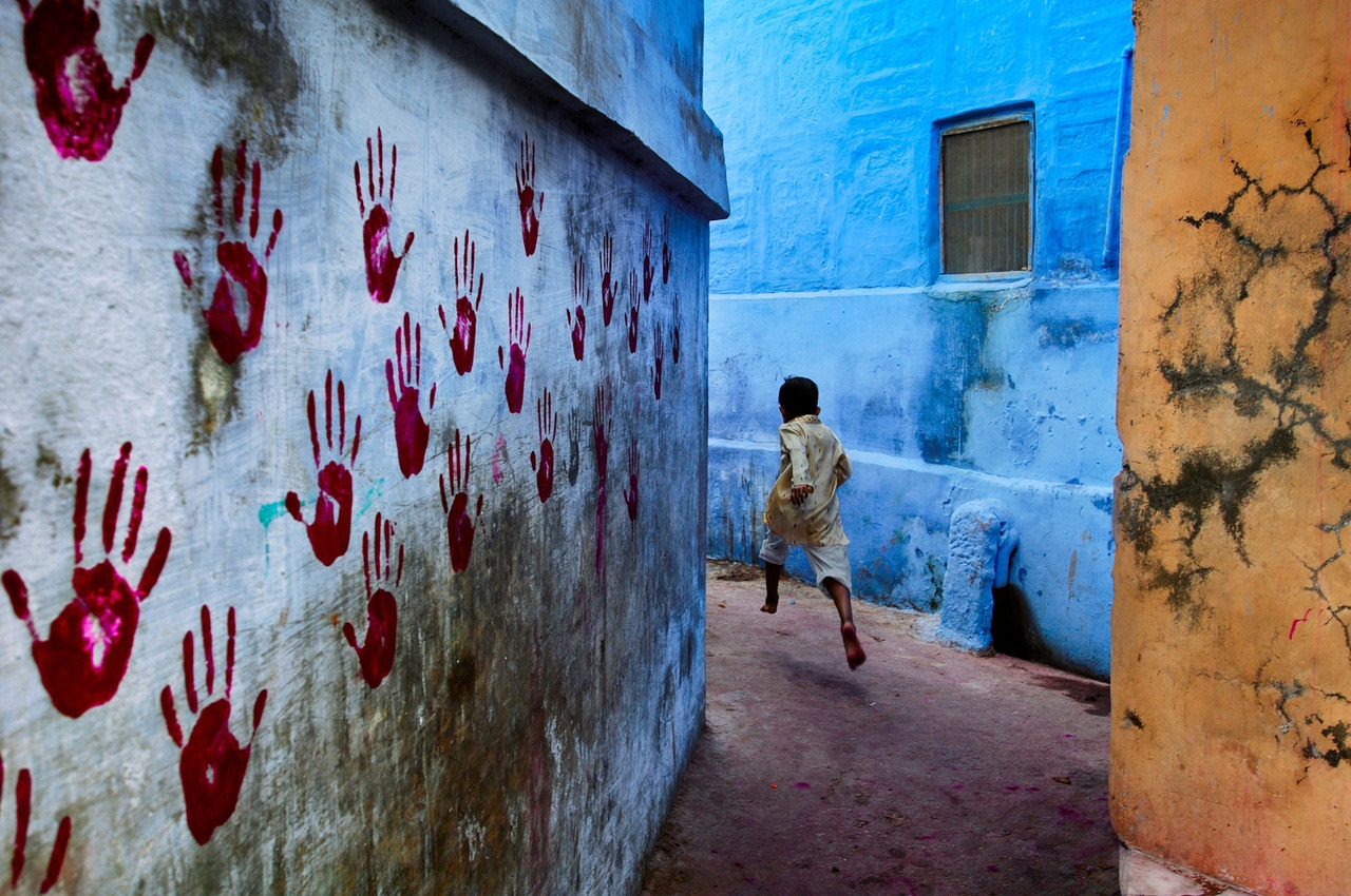 "Boy in mid-flight, Jodhpur, India, 2007 At the foot of the vast Mehrangarh Fort, one can find the Blue City, a small tightly knit maze of houses located towards the north of Jodhpur. In one of the narrow alleyways a boy flees McCurry""s camera. Balancin"