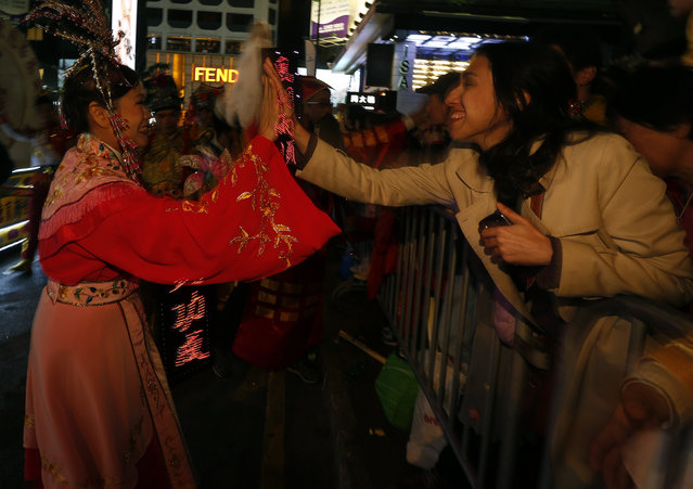 A spectator greets a Chinese dance performer during a Lunar New Year parade celebrating the first da