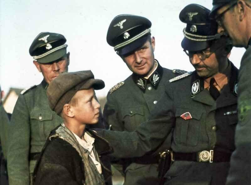 Рейхсфюрер СС Генрих Гиммлер разговаривает с мальчиком из местных жителей во время инспекционной поездки по Белоруссии