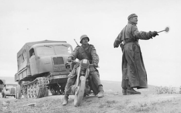 Eastern Front, Operation Citadel, June-July 1943 Motorized elements are advancing toward base areas. Traffic cop belonging to the motorcycle field Feldgendarmerie (military police) is directing traffic.