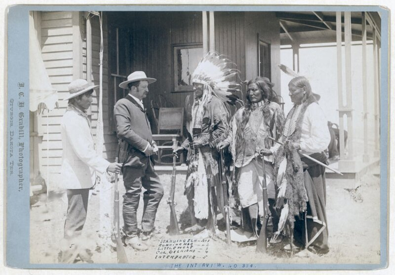 Title: The Interview. Standing Elk, No. 1; Running Hog, No. 2; Little Wolf, No. 3; Col. Oelrich, No. 4; Interpreter, No. 5Three Cheyenne men wearing ceremonial clothing and holding rifles, greeting a Euro-American man in a suit and his interpreter in fr