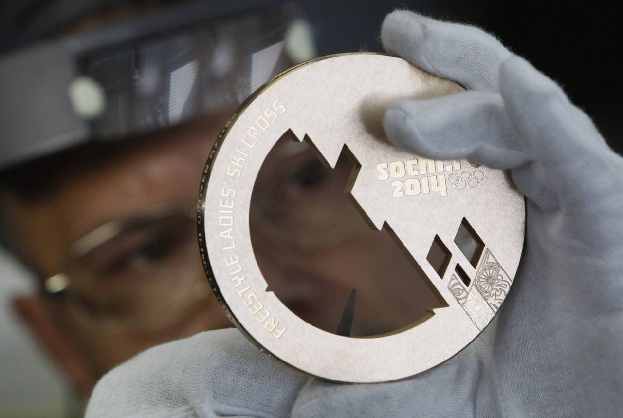 An employee works on a silver medal manufactured for the 2014 Winter Olympic Games in Sochi, at the Adamas jewellery factory in Moscow