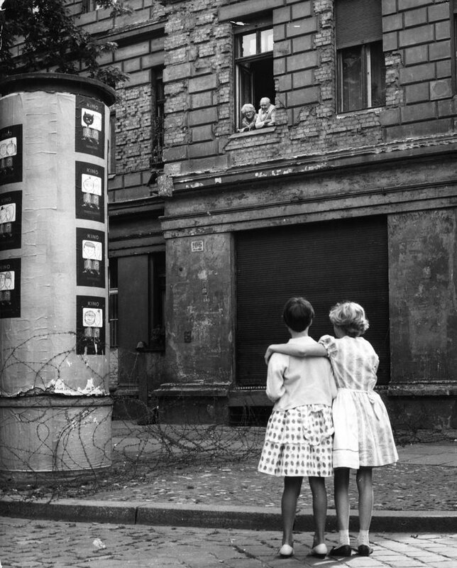 In August 1961, two young girls speak with their grandparents in East Germany over a barbed wire fence, a barricade which later became the Berlin Wall
