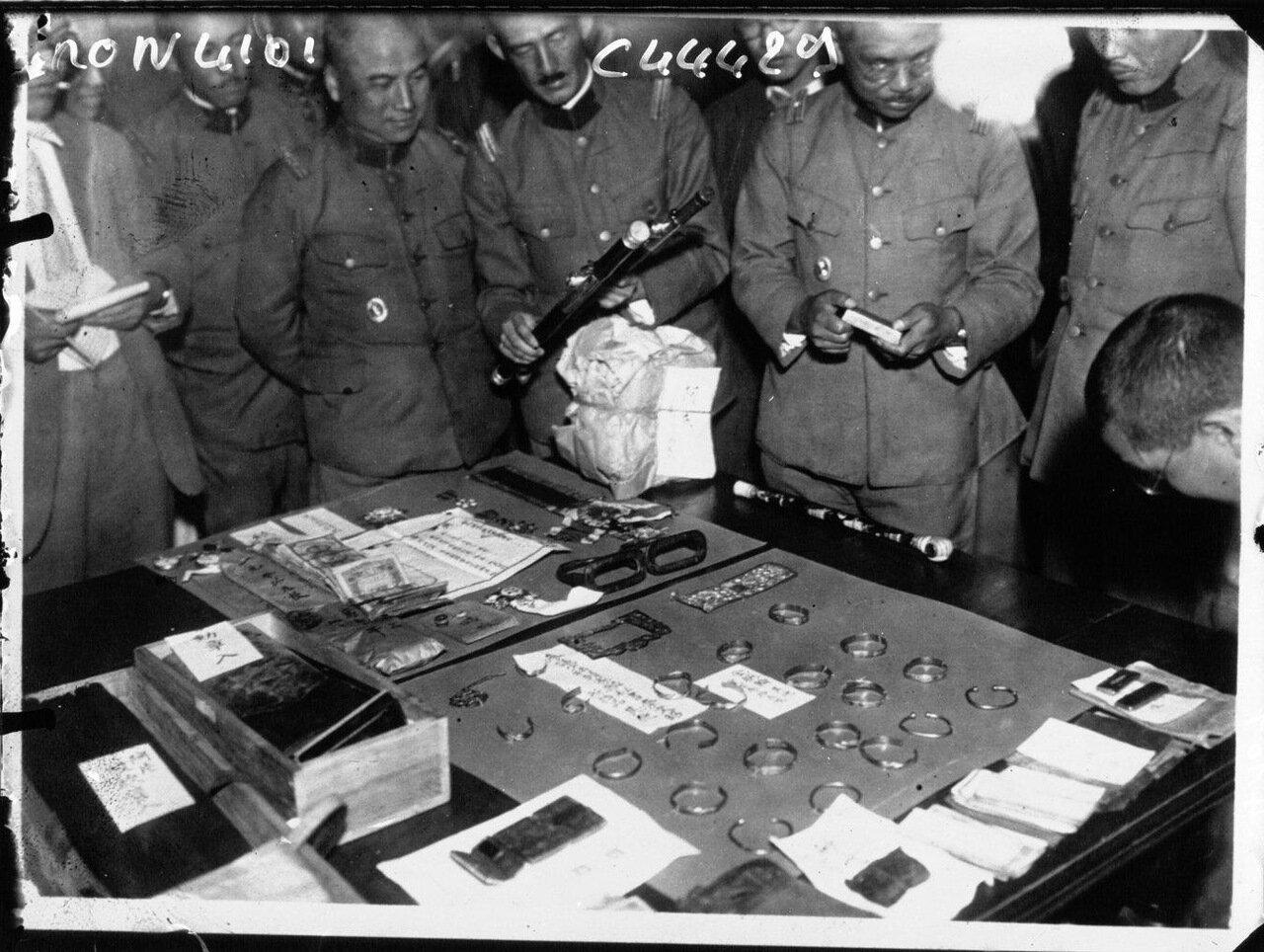 Японские офицеры осматривают личные вещи и золотые браслеты убитого китайского генерала Ма Чанг Чена