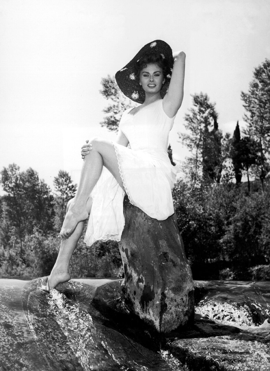 1955: Italian actor Sophia Loren poses barefoot on a rock in a stream in a promotional portrait for the film, 'The Miller's Beautiful Wife', directed by Mario Camerini.