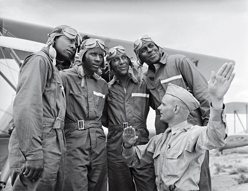 Members of the U.S. Army Air Corps' 99th Pursuit Squadron, the Tuskegee Airmen, receive instruction about wind currents from a lieutenant.