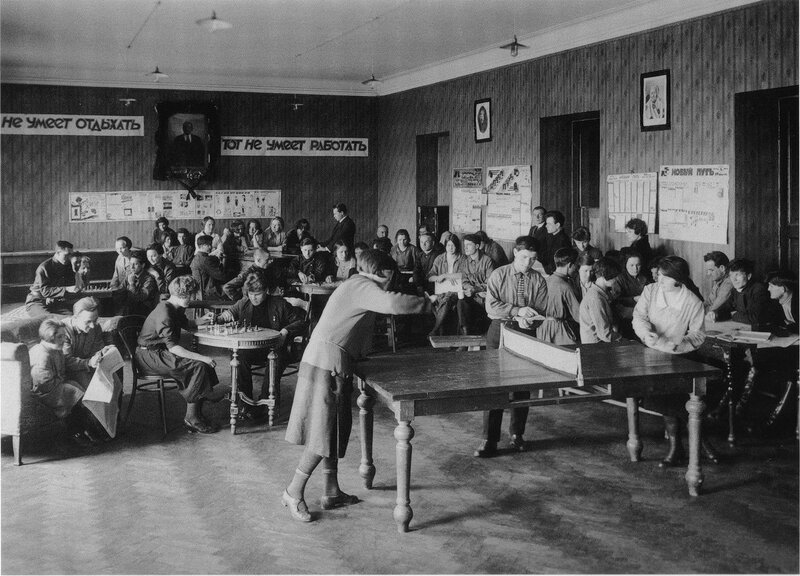 The recreation room of a residential cooperative on the Roshal (Admiralty) Embankment, Leningrad, 1927-28. The banner at the far end of the room reads 'Those who cannot relax cannot work'