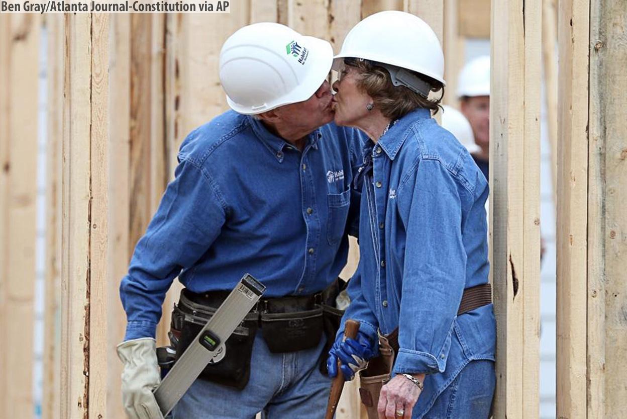 (AP Photo/Mark Humphrey) __Бывший президент Джимми Картер украдкой целует свою жену Розалинн на строительстве a Habitat for Humanity, где они работали 2_11_2015