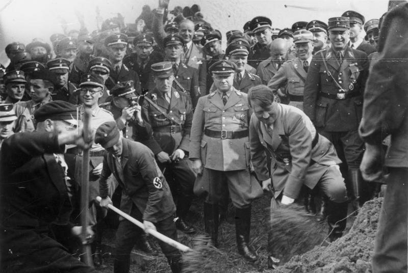 Adolf Hitler shoveling dirt at the ceremonial inauguration of Reichsautobahn construction, 23 September 1933.