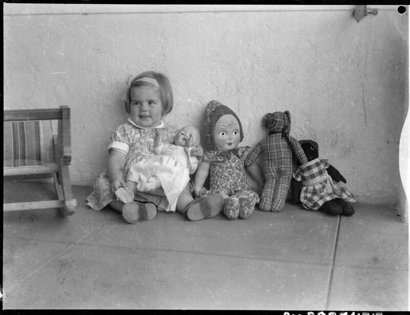 Young child with a baby doll on her lap and a rag doll, a teddy bear and a golliwog next to her, Australia, ca. 1930