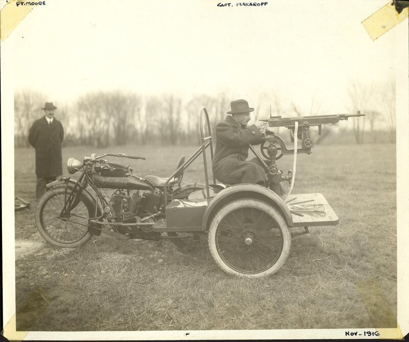Description - A M1895/1914 Colt-Browning machine gun with a Cygnet pedestal mount is mounted on an Indian motorcycle. Capt. Makaroff sits on the pedestal mount as a gunner while Frederick T. Moore looks on.Notes - Inscriptions on front of photo identify