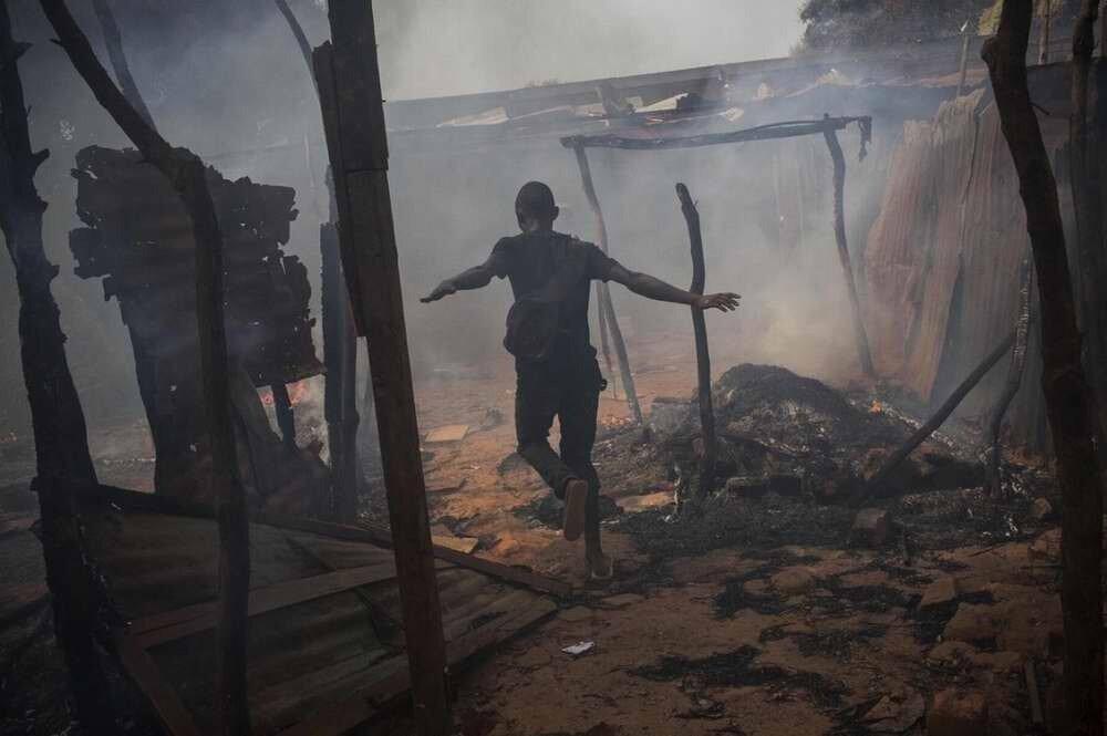 Один из представителей христианского большинства в столице Центрально-Африканской республике городе Банги радостно бежит через разграбленные и подожженные дома мусульман