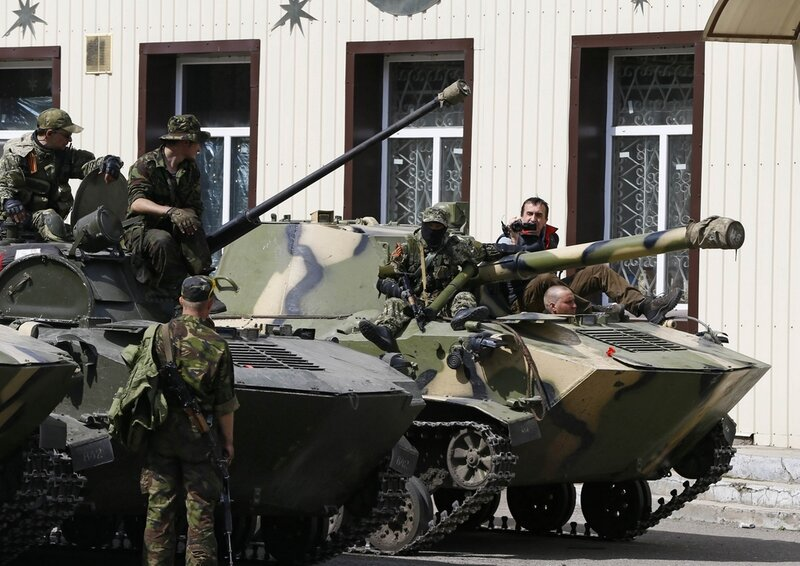 Armed men sit on armoured personnel carriers in Slaviansk