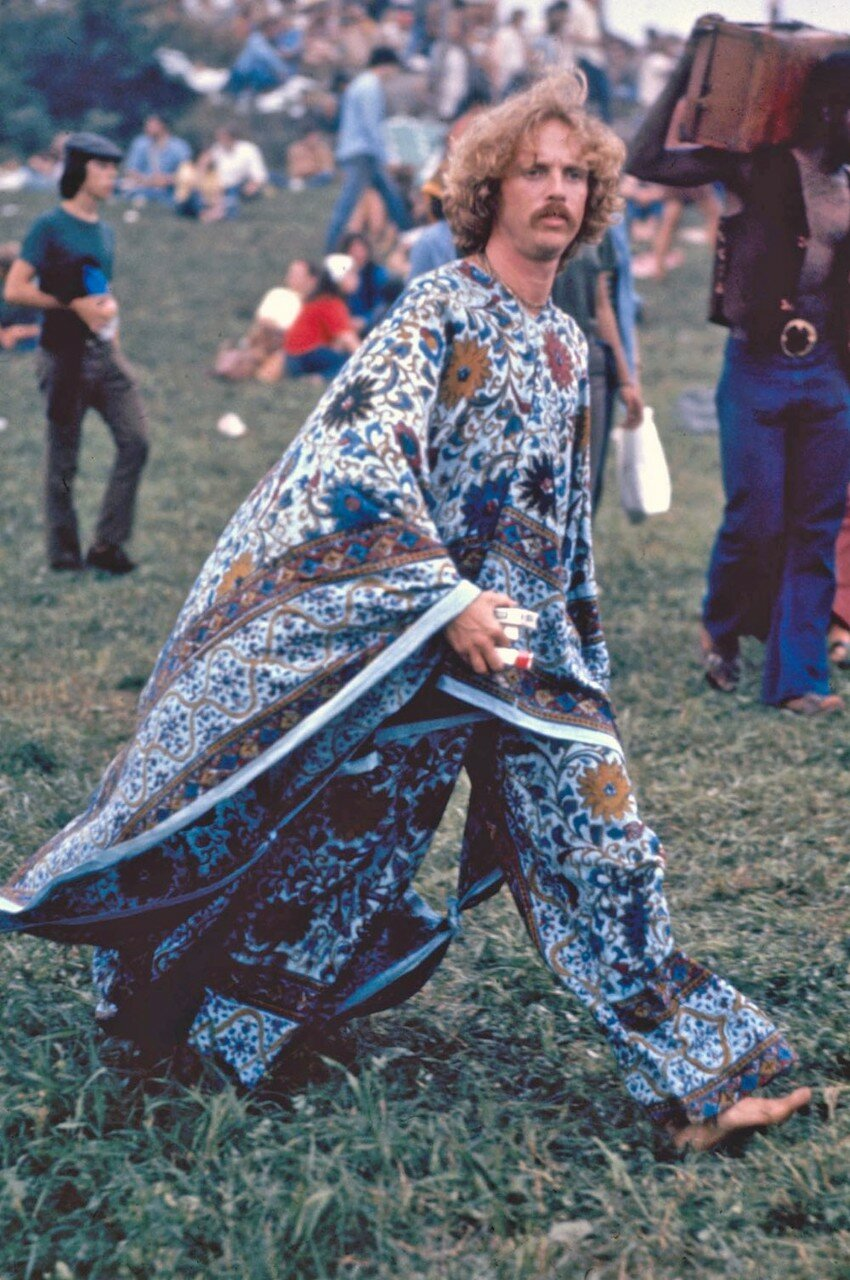 Hippie in flowing robes walking around crowd at Woodstock