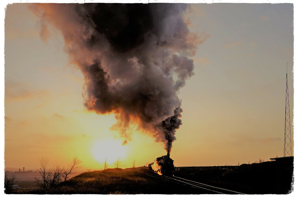 Chris Davies - Gently edging up the steep incline, an SY locomotive laden with underground mine waste nears its destination to dump the spoil in a golden winter sunset. Fuxin, Liaoning Province, China.